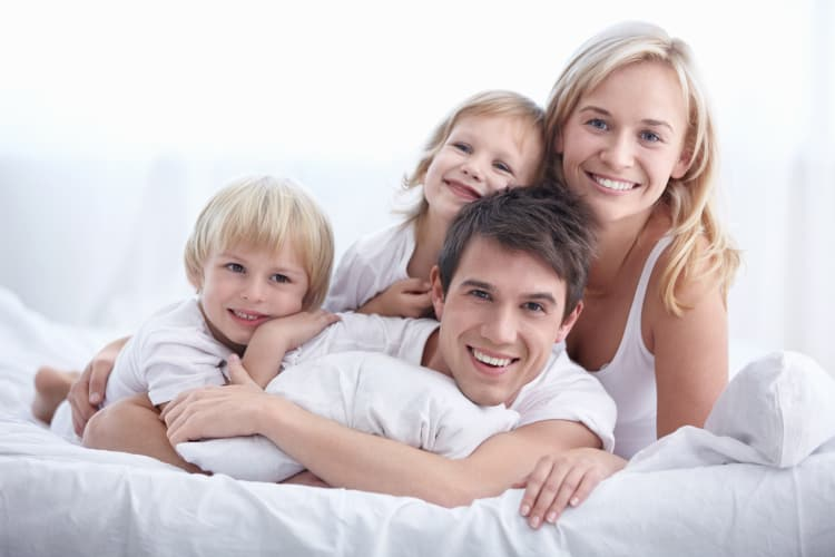 family smiling on bed